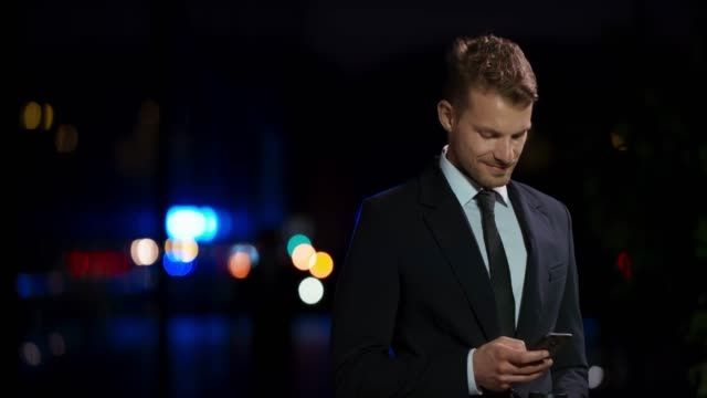ld young caucasian business man standing outside at night and typing on his smartphone - holding stock videos & royalty-free footage