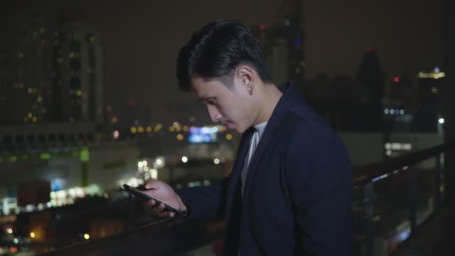 vídeos de stock, filmes e b-roll de homem de negócio caucasiano novo de d que está fora na noite e que datilografa em seu smartphone - touch screen