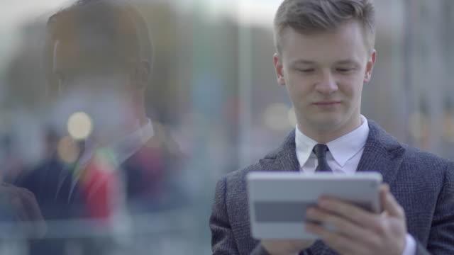 vídeos de stock e filmes b-roll de young caucasian businessman using digital tablet computer browsing the web in the city - camisa e gravata