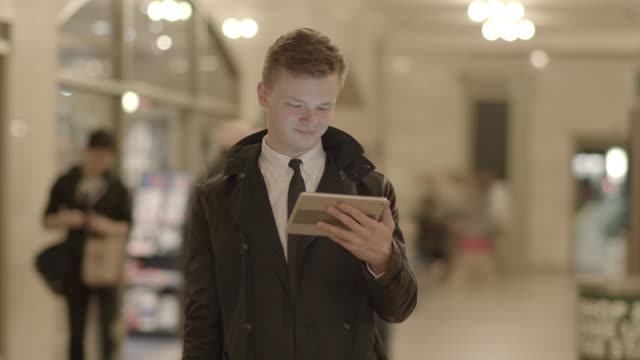 young caucasian businessman using digital tablet computer browsing the web in the city - choosing stock videos & royalty-free footage