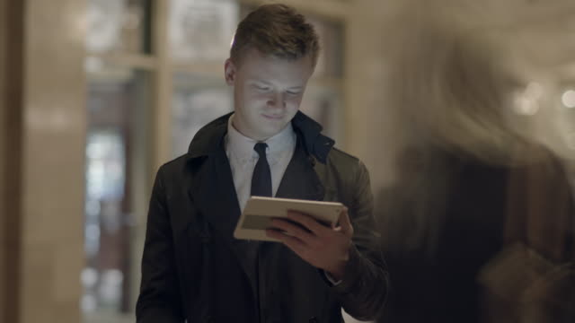 young caucasian businessman using digital tablet computer browsing the web in the city - giacca e cravatta video stock e b–roll