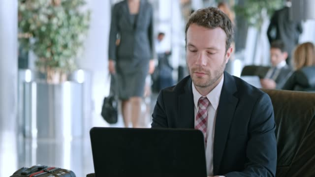 ds young caucasian businessman working on his laptop in the business lounge at the airport - slovenia stock videos & royalty-free footage