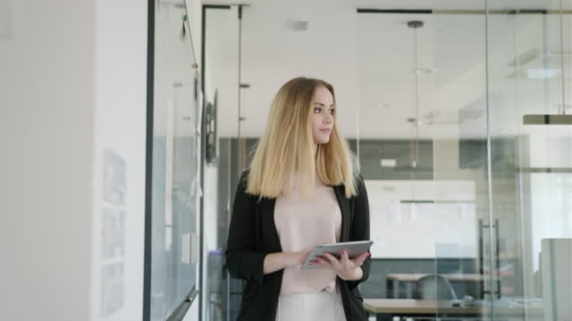 young caucasian businesswoman at work with digital tablet - medium shot stock videos & royalty-free footage