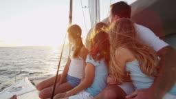 Young Caucasian family outdoors enjoying sunset yacht vacation
