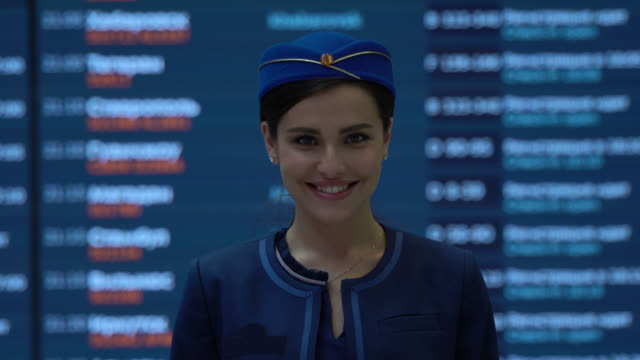 young caucasian flight attendant facing camera smiling standing in front of the flight schedule screen - crew stock videos & royalty-free footage