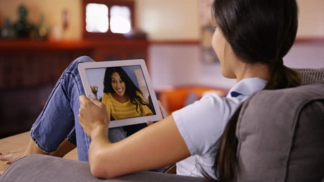 young caucasian girl video chats with her friend on her tablet - mixed race person stock videos & royalty-free footage