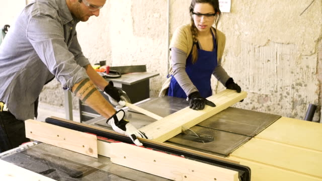 Junge kaukasischen Männer und junge Hispanic Frau Schneiden board mit table saw
