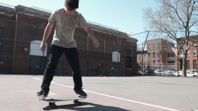 vídeos y material grabado en eventos de stock de a young, caucasian male skateboards at a brooklyn, nyc skatepark - truco