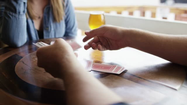 vídeos de stock e filmes b-roll de a young caucasian man deals playing cards to a young caucasian woman with beer next to a window at a bar - carta de baralho