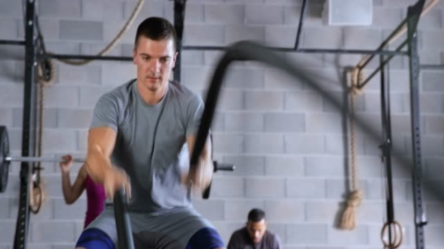young caucasian man doing a battle rope exercise in the fitness center - rope stock videos & royalty-free footage