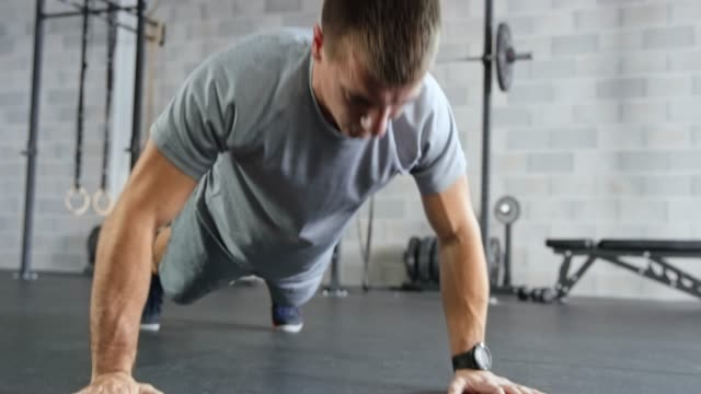 young caucasian man doing push ups in the fitness center - push ups stock videos & royalty-free footage