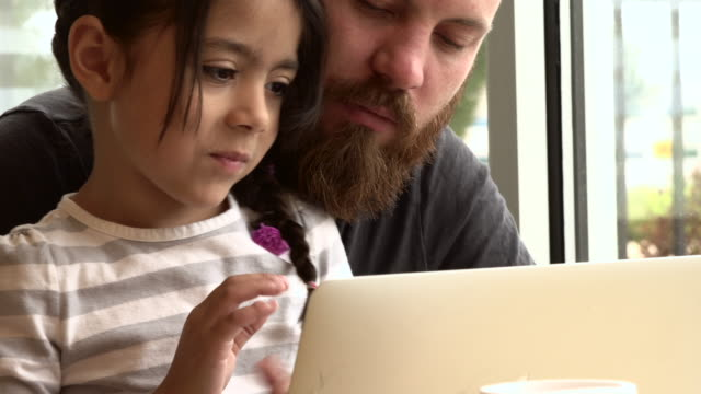 Young Caucasian Man Helping Little Hispanic Girl with Laptop