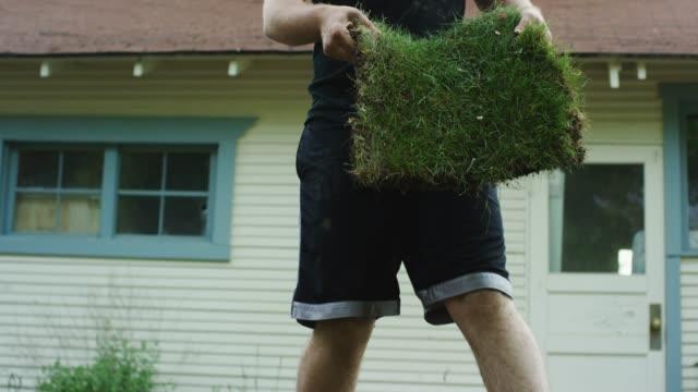 vídeos de stock e filmes b-roll de a young caucasian man in causal clothing lays a square of sod in a residential backyard - relvado terra cultivada