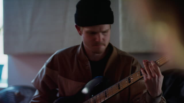 a young caucasian man in his twenties plays the electric bass guitar while a young hispanic man in his thirties with a beard mimes playing the drums while playing music together in a recording studio - trommel stock-videos und b-roll-filmmaterial