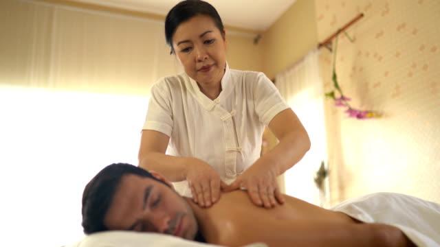 ung kaukasisk man slappna av under massage - massage table bildbanksvideor och videomaterial från bakom kulisserna