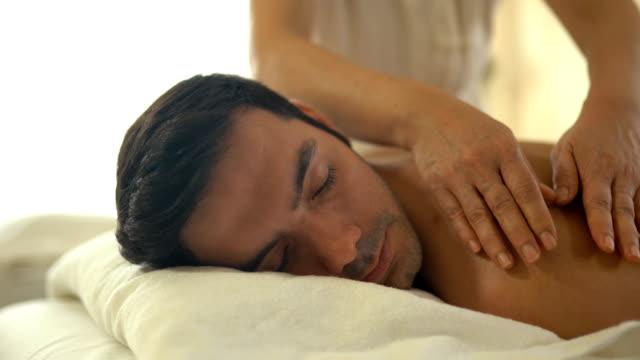 vidéos et rushes de jeune homme caucasien se détendre pendant le massage - massage table