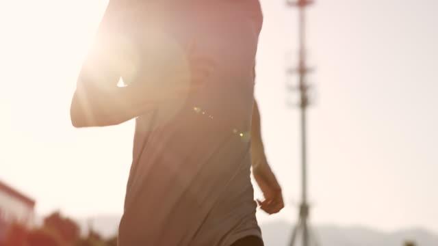 SLO MO DS TU jungen kaukasischen Mann läuft im Stadion bei Sonnenuntergang