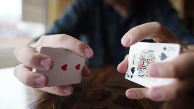 Ein junger Mann der kaukasischer mischt ein Kartenspiel neben einem Fenster