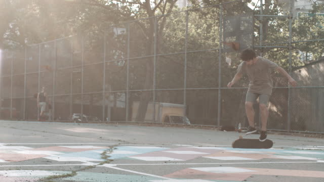a young caucasian man skateboards through the streets of brooklyn, nyc - 柵点の映像素材/bロール
