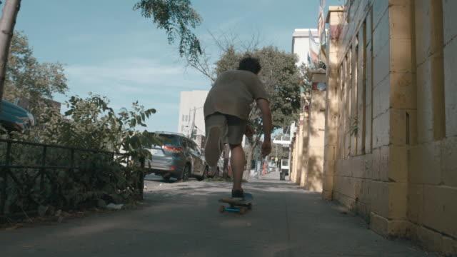 vídeos y material grabado en eventos de stock de a young caucasian man skateboards through the streets of brooklyn, nyc - sólo hombres jóvenes