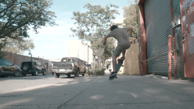 A young, caucasian man skateboards through the streets of Brooklyn - slow motion