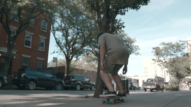 vídeos y material grabado en eventos de stock de a young, caucasian man skateboards through the streets of brooklyn - slow motion - sólo hombres jóvenes