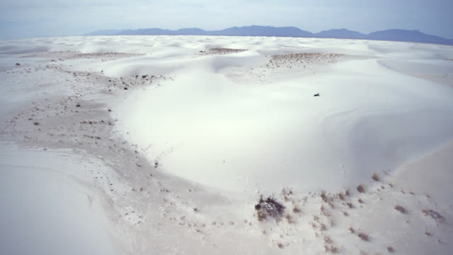 Young Caucasian man, tourist with the big backpack, resting on the top of the dune in the sandy desert. White Sands National Monument, New Mexico, USA. Aerial drone footage.
