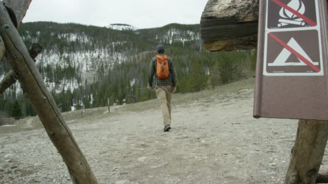 """a young caucasian man wearing a backpack walks past a """"no campfires"""" and """"no camping"""" signs to hike in the rocky mountains of colorado under an overcast sky in winter - forbidden stock videos & royalty-free footage"""
