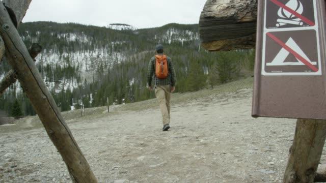 冬の曇り空の下でコロラドのロッキー山脈でハイキングするためにバックパックを着た若い白人男性は、「ノーキャンプファイヤー」と「キャンプなし」の看板を歩いています - 禁止点の映像素材/bロール