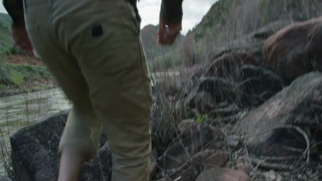 a young caucasian man wearing a backwards baseball cap and sandals hikes through brush at the edge of the colorado river in western colorado - trousers stock videos & royalty-free footage