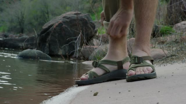 A Young Caucasian Man Wearing Sandals on a Concrete Boat Ramp Bends down to Roll Up His Khaki Pant Legs Next to the Colorado River in Western Colorado