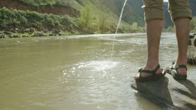 a young caucasian man wearing sandals standing on a rock urinates into the colorado river in western colorado on a sunny day - river colorado stock videos & royalty-free footage