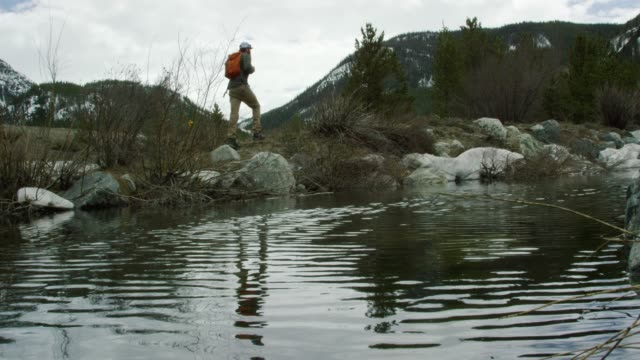 a young caucasian man with a beard and a backpack hikes next to a snowy mountain stream/lake in the rocky mountains of colorado under an overcast sky in winter - rocky mountains north america stock videos & royalty-free footage
