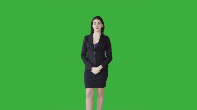 young caucasian manager standing isolated against green screen. good-looking brunette businesswoman talking in front of green background. - hand heben stock-videos und b-roll-filmmaterial