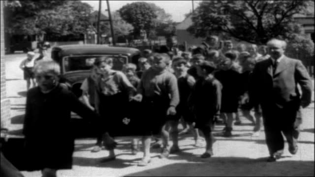 vídeos de stock e filmes b-roll de young caucasian students jump up from desks in classroom / caucasian children run along country road, chasing after automobiles with nsv badge /... - nazismo
