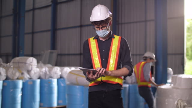 young caucasian warehouse employee using digital tablet for checking stock in the factory - examining stock videos & royalty-free footage