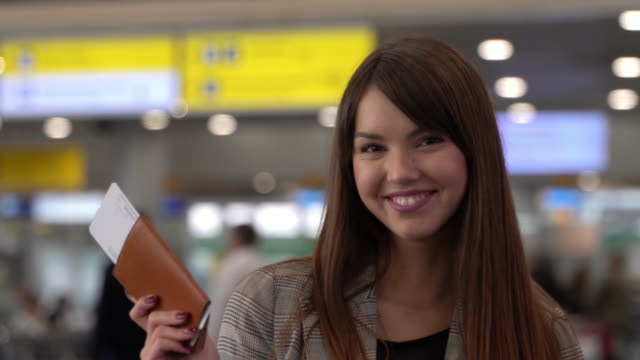 young caucasian woman at the airport facing camera with a toothy smile while showing her passport and boarding pass - passport stock videos & royalty-free footage