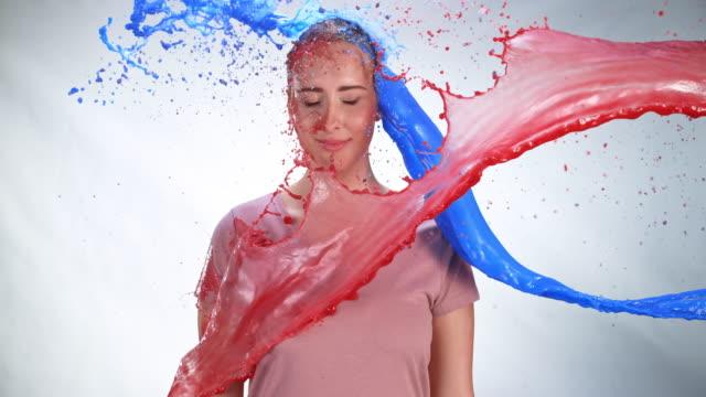 赤と青のペンキでシャワーを浴びている SLO MO LD 若い白人女性