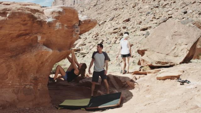 stockvideo's en b-roll-footage met 4 k slo mo: jonge kaukasische vrouw klimmen een rotsblok - boulder