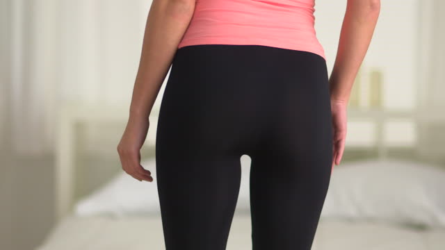 Young Caucasian woman dancing in yoga pants from behind
