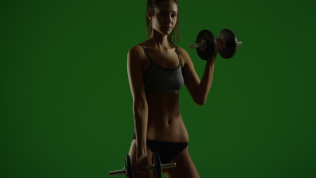 young caucasian woman dramatically lifts weights on green screen - 人の腕点の映像素材/bロール