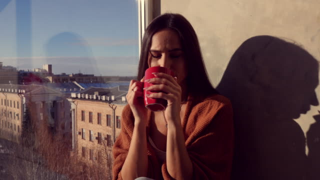 Young Caucasian woman drinking a cup of coffee while sitting on the windowsill with a panorama of city