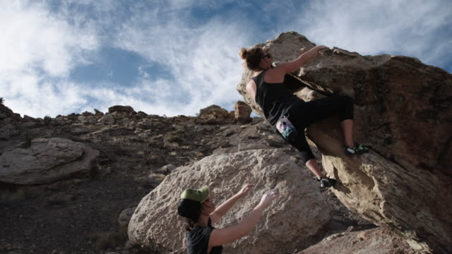Young Caucasian Woman Free Climbs a Rock Face While A Young Latina Woman Spots Her