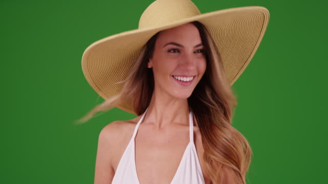 young caucasian woman in bikini posing with floppy hat on green screen - sonnenhut stock-videos und b-roll-filmmaterial