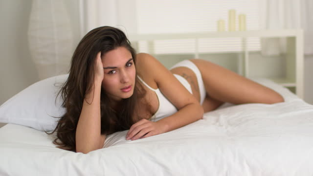 young caucasian woman lying on bed in lingerie - 10 sekunden oder länger stock-videos und b-roll-filmmaterial