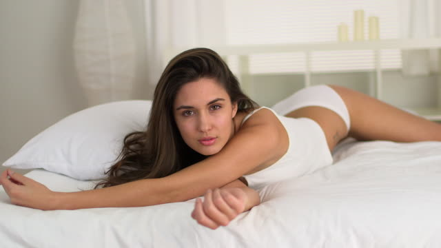 stockvideo's en b-roll-footage met young caucasian woman lying on bed in lingerie - mooie mensen
