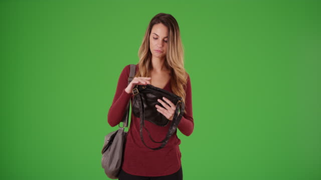 young caucasian woman picking out a new purse or bag on green screen - menschliches gelenk stock-videos und b-roll-filmmaterial