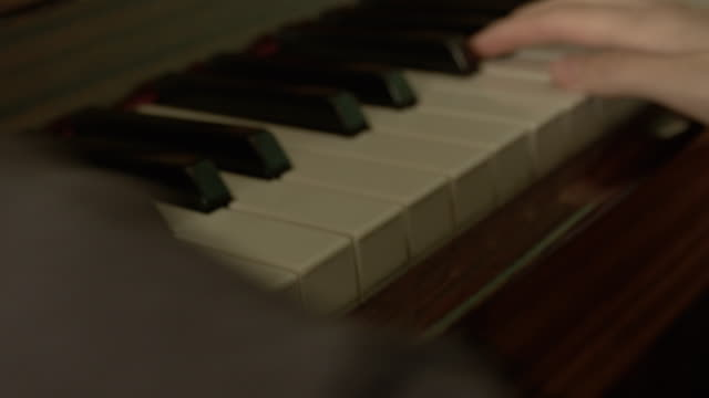 young caucasian woman plays the piano.  close-up side view. graceful fingers smoothly press the keys of a vintage piano. - piano stock videos & royalty-free footage