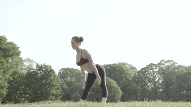 a young, caucasian woman practices yoga in the outdoors - 4k - slow motion - legs apart stock videos and b-roll footage
