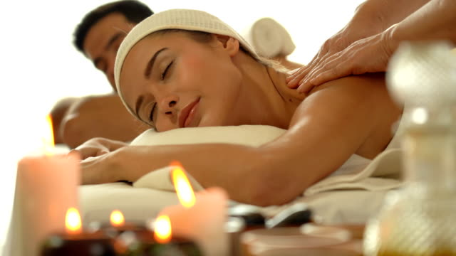 vídeos y material grabado en eventos de stock de joven mujer caucásica relajarse durante el masaje - dar masajes